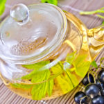 Tea with black currants in glass teapot on bamboo napkin